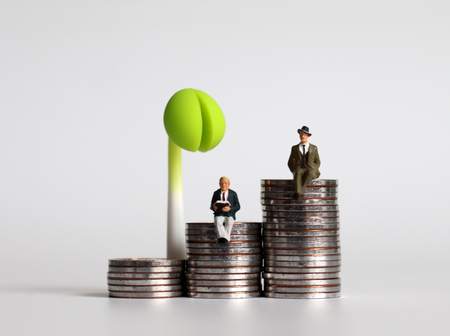 Three piles of coins and a sprout. Two miniature business men sitting on a pile of coins. Imagens