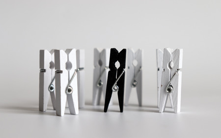 Many white tongs that surrounds one black tongs.