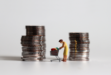 A miniature woman shopping among a pile of coins. Stock fotó