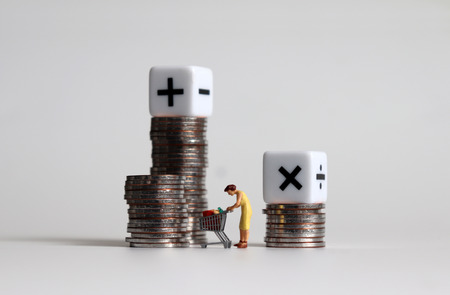 A miniature woman with a shopping cart between two piles of coins and two arithmetic operator cube.