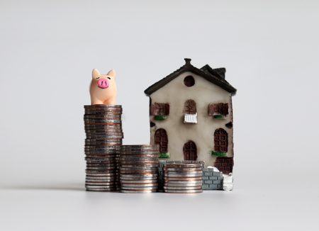 A pink pig on three piles of stepped coins in front of a miniature house.