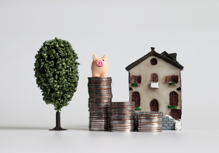 A pink pig on three pile of stepped coins in front of a miniature house with a miniature tree.