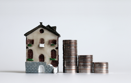 Miniature house and three piles of stepped coins.