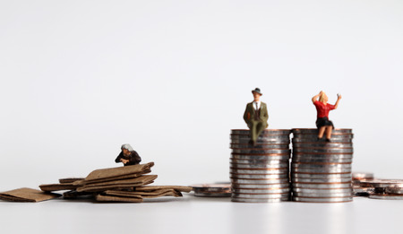 Monedas con personas en miniatura. El concepto de brecha generacional entre ricos y pobres. Foto de archivo