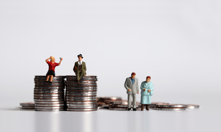 Coins and miniature people. The concept of economic generational conflict. Stockfoto