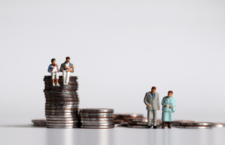 Coins and miniature people. The concept of income and generation gap. Stockfoto