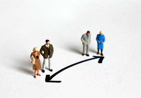 Miniature people who stand in a different direction. Banco de Imagens - 121961148