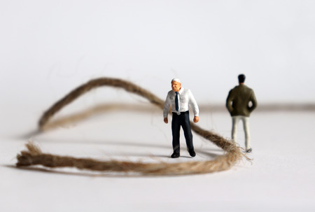 Two miniature men standing on the side of the rope. The concept of intergenerational discord.
