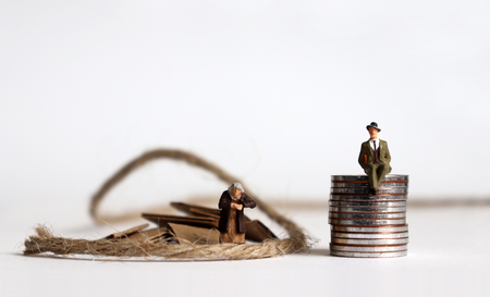 Coins with miniature people. The concept of the generation gap between rich and poor. Фото со стока