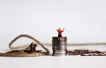 Coins with miniature people. The concept of people spending their old age in poverty.