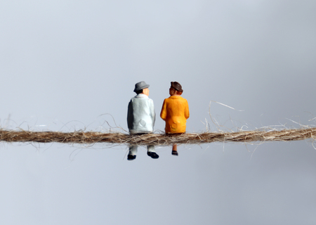 The back of a miniature elderly couple sitting on a rope. The concept of old age and destitution. Stock Photo - 122052971