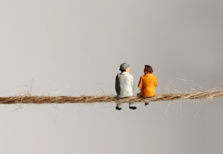 The back of a miniature elderly couple sitting on a rope.