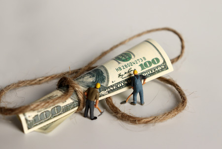 A hundred-dollar bill tied to a rope and miniature people.