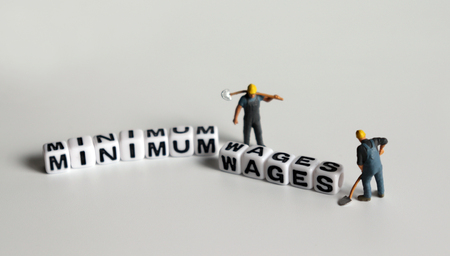 MINIMUM WAGES word in white cube. Miniature people.
