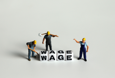 'WAGE' word in white cube. Miniature people.