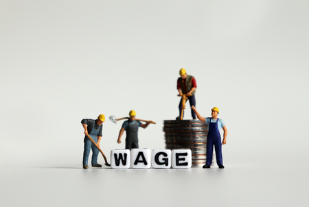 WAGE word in white cube. Miniature people and pile of coins.