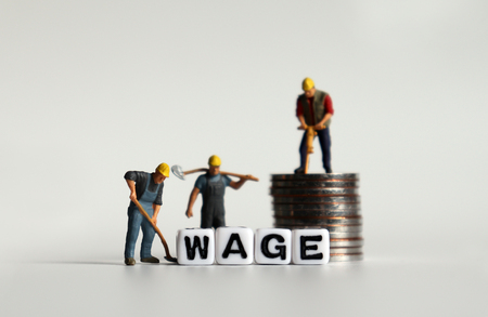 WAGE text in white cube. Miniature people and pile of coins.