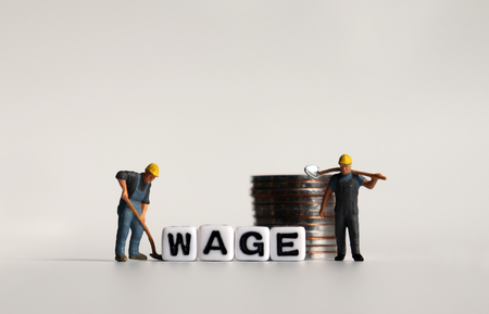 WAGE text in white cube. Miniature worker and pile of coins. Imagens