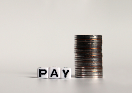 PAY text in white cube and a pile of coins.