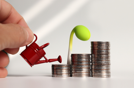 A hand holding a watering can and three piles of stepped coins. Stock Photo
