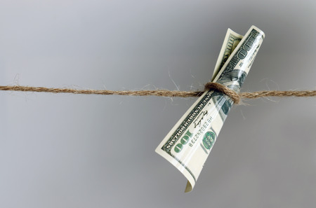 A hundred dollar bill hanging from a rope. 免版税图像 - 121961264