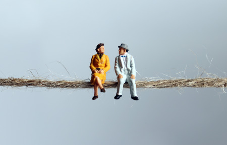 A miniature elderly couple sitting on a rope. Stock Photo