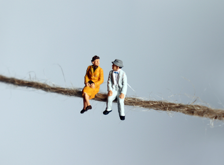 A miniature elderly couple sitting on a rope. Concepts on the deficient measures of an aging society.