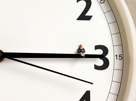 A miniature man sitting on a clock and reading a book.