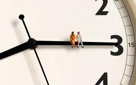 A miniature old couple sitting on a clocks needle. Фото со стока