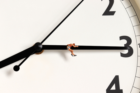 A miniature woman hanging from a clock needle. Фото со стока