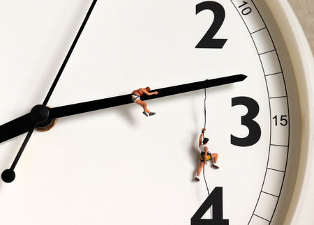 Two miniature women hanging from a black clock needle. Stock Photo