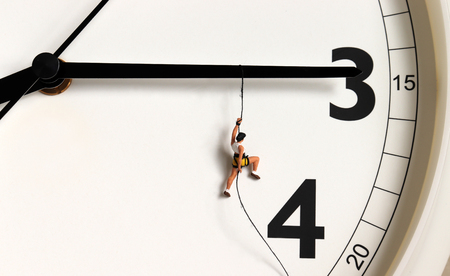 A miniature climber hanging by a rope on a black watch needle. Фото со стока