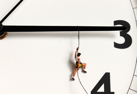 A miniature climber hanging by a rope on a black watch needle. Imagens