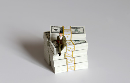 A miniature man sitting on a pile of hundred dollar bills.