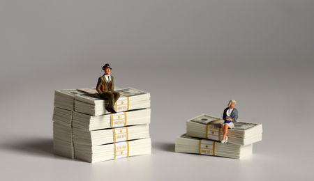 A miniature man and a miniature woman sitting on a pile of hundred-dollar bills of different heights. Foto de archivo