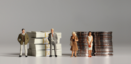 A pile of hundred dollar bills and coins with miniature people. The concept of a pay gap between men and women.