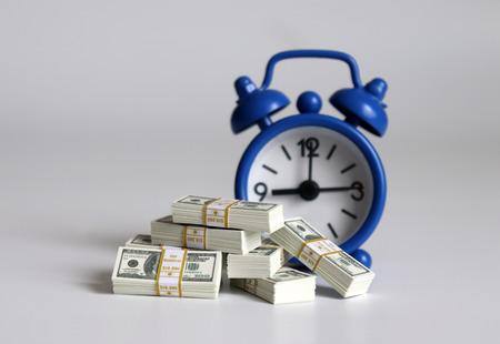 Money bundles of hundred dollars in front of a blue alarm clock.
