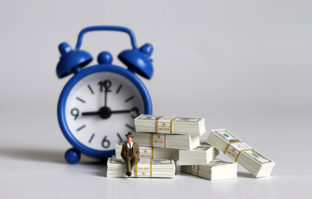 A miniature man sitting on a wad of $ 100 bills in front of a blue alarm clock.