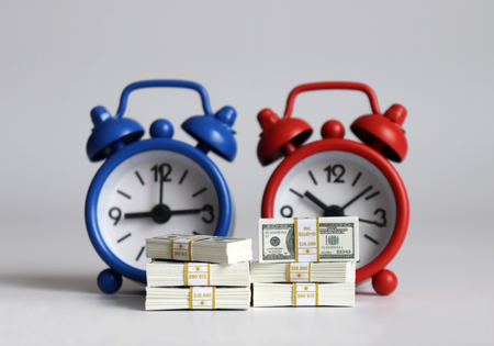 Bunch of $ 100 bills in front of two alarm clocks. 写真素材