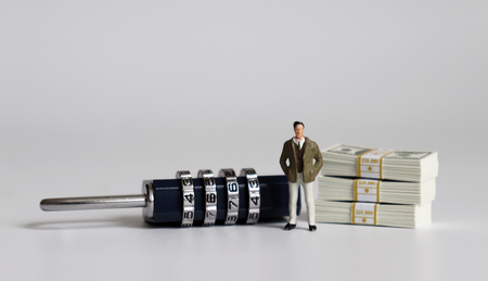 A miniature man standing with a combination lock and wad of bills.