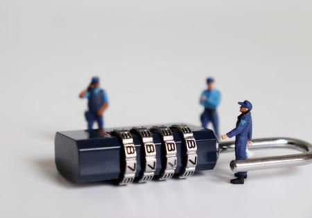 Una cerradura de combinación y personas en miniatura.