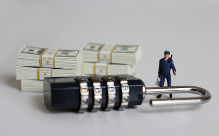 The bundle of bills and a combination lock. Miniature people.