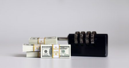 A combination lock and bundle of hundred dollar bills. Concepts about safe financial transactions.
