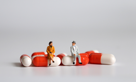 Miniature people sitting on pills. The concept of old people and health care.