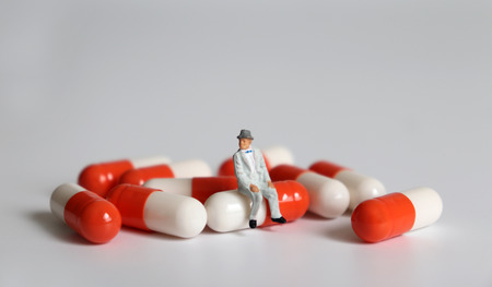 A miniature old man sitting on a pill.