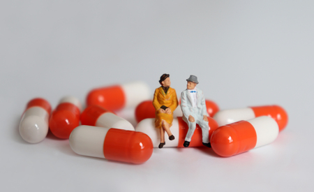 A miniature old couple sitting on a pill.