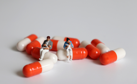A miniature woman and a miniature man sitting on a capsule holding a baby.