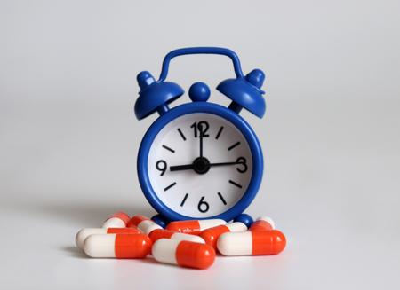 Blue alarm clocks and pills. Banco de Imagens