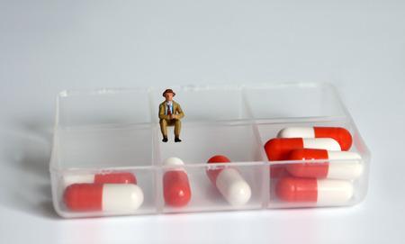A miniature man sitting on a medicine case.