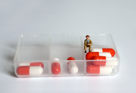 A miniature man sitting on a medicine case.